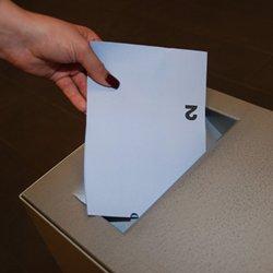 Einwerfen von Wahlzettel in Wahlurne